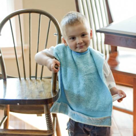 Toddler wearing blue terry towel baby bib by Bababean